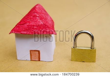 A small and beautifl house model concept of good segurity with a lock padlock, property protection.