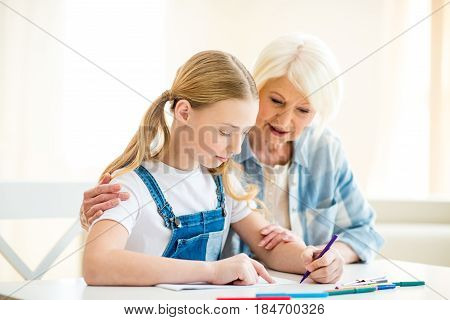 Smiling Senior Woman And Preteen Girl Drawing Together At Table