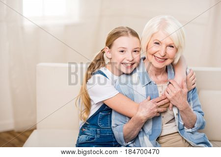 Happy Grandmother And Granddaughter Hugging And Smiling At Camera
