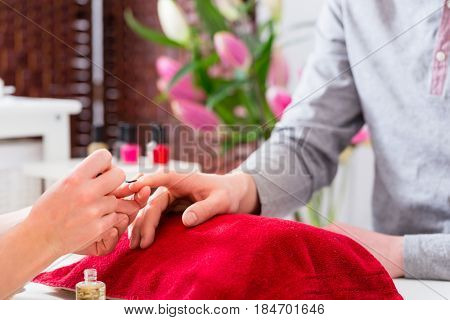 man receiving manicure in beauty parlor, her nails being polished