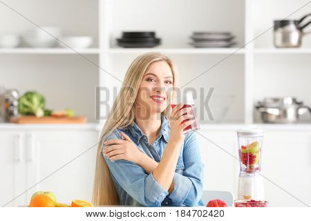 Beautiful young woman with glass of fresh juice in kitchen