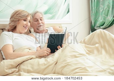 Elderly couple reading book while resting in bed at home