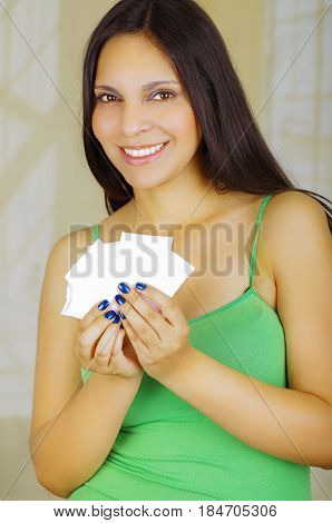 Young beautiful woman with a green blouse holding a couple of hygenic towels.