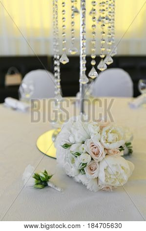 A bouquet of a bride from white roses and peonies and a groom's boutonniere lie on a decorated table. Focus on bouquet and boutonniere
