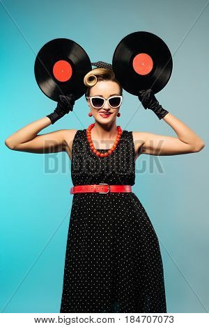 Pretty pin-up woman with retro hairstyle and make-up posing with vinyl record blue vintage background.