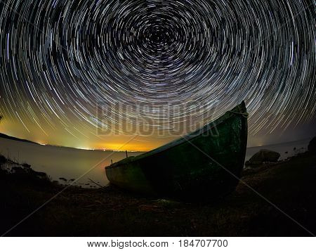 beautiful sky at night with startrails over the lake and silhouette of fishing boat