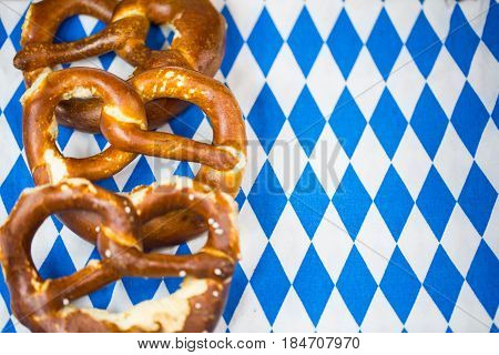 Pretzel on white / blue background. Rhombuses Bavarian colors