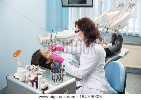 Female Dentist With Dental Tools - Mirror And Probe Checking Up Patient Teeth At Dental Clinic Offic