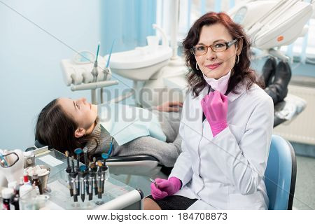 Portrait Of Friendly Female Dentist With Patient In The Chair At The Dental Office. Doctor Wearing G