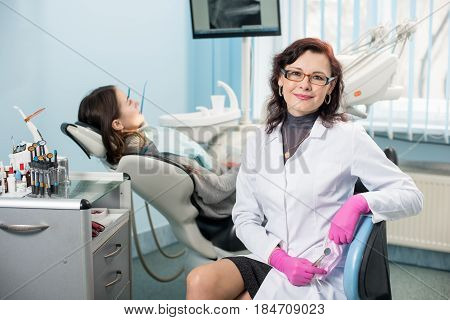 Portrait Of Friendly Woman Dentist With Patient In The Dental Office. Doctor Wearing Glasses, White