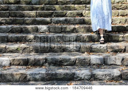 Woman legs going down the old stair way