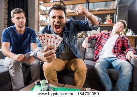 Triumphing young man sitting on sofa and showing street flash of diamonds combination