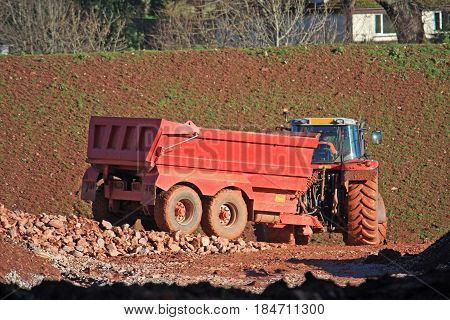 Tractor towing a tipper trailer on a construction site