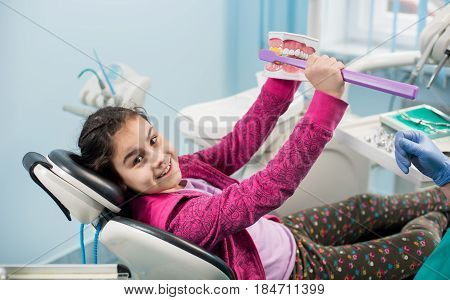 Smiling Girl In Dentist Chair Showing Proper Tooth-brushing Using Dental Jaw Model And Big Toothbrus