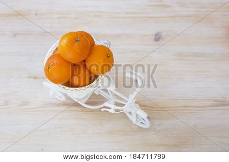 Mandarins or clementines in white bike basket concept