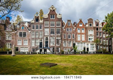 Begijnhof houses and garden in Amsterdam, Netherlands. The Begijnhof is one of the oldest inner courts in the city of Amsterdam