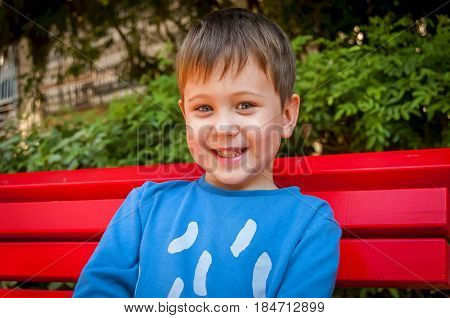 Happy smiling Caucasian kid sitting on the bench.