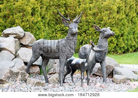 Statue of the deer in the park. Male deer protecting his family.