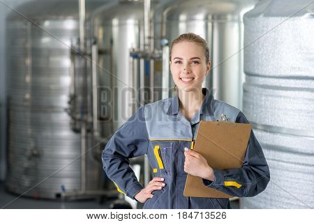 Specialist at a water factory with equipment on the background.
