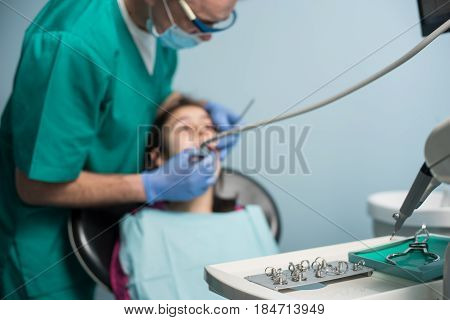 Young Girl On The First Dental Visit. Senior Pediatric Dentist Treating Patient Girl Teeth At The De