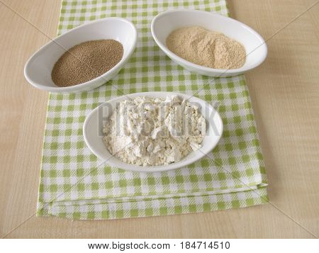 Flour, sourdough extract and bakers yeast in bowls