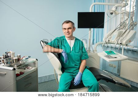 Portrait Of Handsome Male Dentist In The Morden Dental Office. Doctor Wearing Green Uniform, Blue Gl