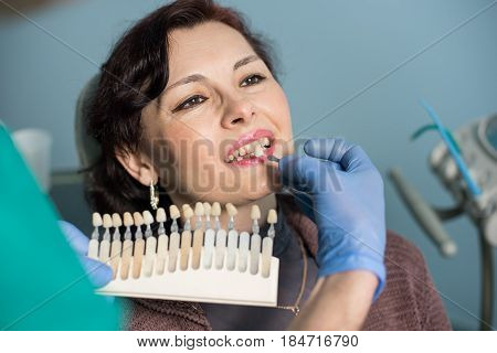 Close-up Portrait Of Woman In Dental Clinic Office. Dentist Checking And Selecting Colour Of The Tee