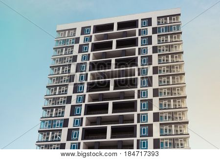 From below shot of modern and new apartment building. Photo of a tall block of flats with balconies against a blue sky.