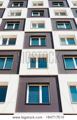 From below shot of modern and new apartment building. Photo of a tall block of flats against a blue sky.