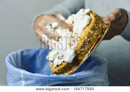 closeup of a young caucasian man throwing a cake topped with whipped cream to the trash bin