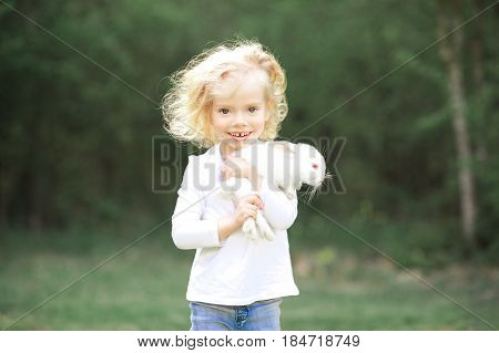 Smiling baby girl 3-4 year old holding white rabbit outdoors. Looking at camera. Childhood. Summer time.