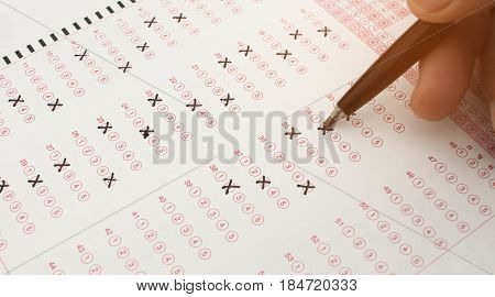 student holding pen for testing in exercise exams answer sheets and checkbox for final exams test in school
