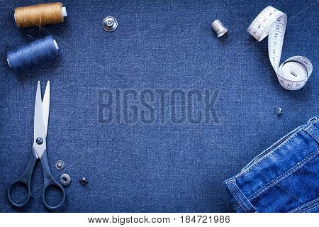 Needlework: Scissors Button Thread Thimble Centimeter Tape And Jeans On Background Of Dark Blue Gray Jeans Fabric Top View.