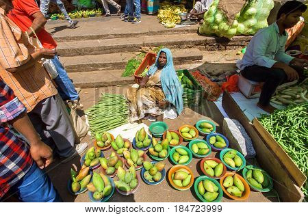 BANGALORE, INDIA - FEB 12, 2017: Elderly woman vendor selling green avocado and other fruits from ground on February 12, 2017. Capital of the state Karnataka has a population of 8.42 million
