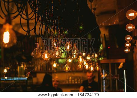 Decorative antique edison style light bulbs against woden wall background.