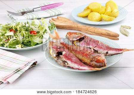 Baked red mullet served with boiled potatoes and green salad. Rustic style.
