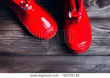 Red Rubber boots for rainy day on wooden background. Autumn kids boots concept