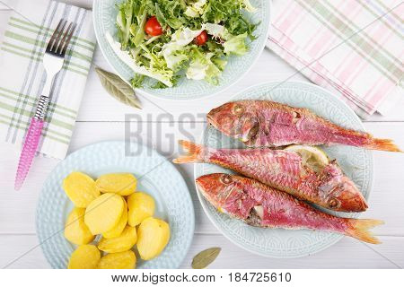 Baked red mullet served with boiled potatoes and green salad. Rustic style. Top view.