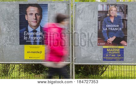 FRANCEMAY 032017: A blurred woman walking past electoral posters displaying the remaining two French presidential candidates Emmanuel Macron and Marine Le Pen which will compete for the second round on May 7 2017.