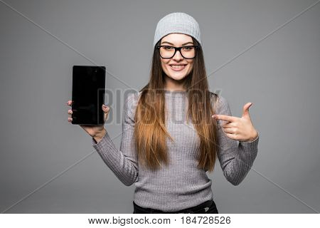 Portrait Of Cheerful Hipster Woman Pointing Finger On Tablet Computer Screen Over Gray Background