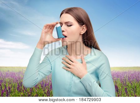 Young woman using asthma inhaler outdoor