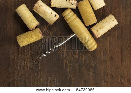 A photo of an old-fashioned corkscrew with corks, shot from above on a dark wooden background texture with copy space. A design template for a wine list or a tasting invitation