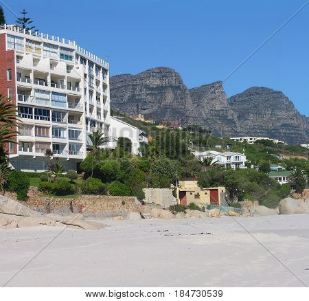 CLIFTON, CAPE TOWN, SOUTH AFRICA, BEACH AND BUILDINGS IN FORE GROUND, WITH MOUNTAINS IN THE BACK GROUND