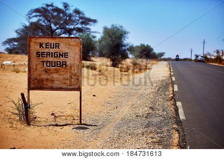 signpost to touba in senegal, background blurry desert landscape.