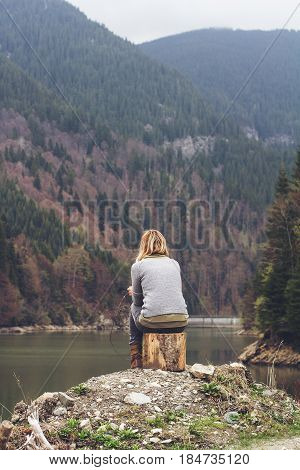 rear view of Caucasian young blonde woman with light colored sweater meditating relaxing sitting alone on a tree stump in front of a lake surrounded by forest mountains copyspace