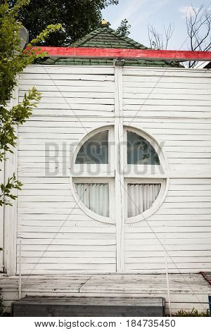 small white wooden house with round window