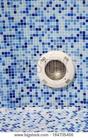 small tiles and round light in empty pool background