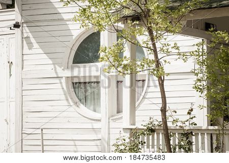 small white wooden house with round window and tree infront