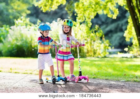 Kids Riding Scooter In Summer Park.