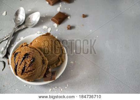 Chocolate ice cream in a plate with chocolate sauce and